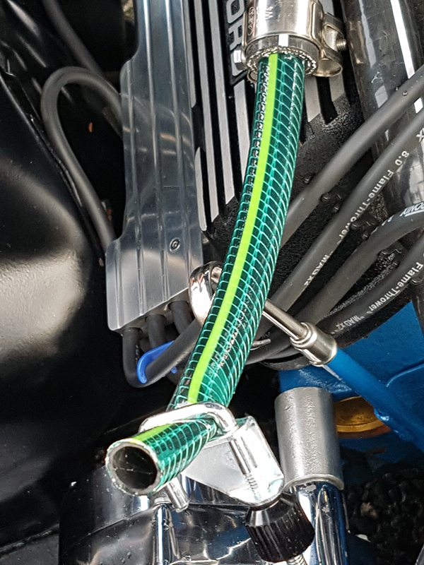 The garden hose pipe was then wedged into the old heater hose that was now attached to the water elbow, then the water was run into the block.